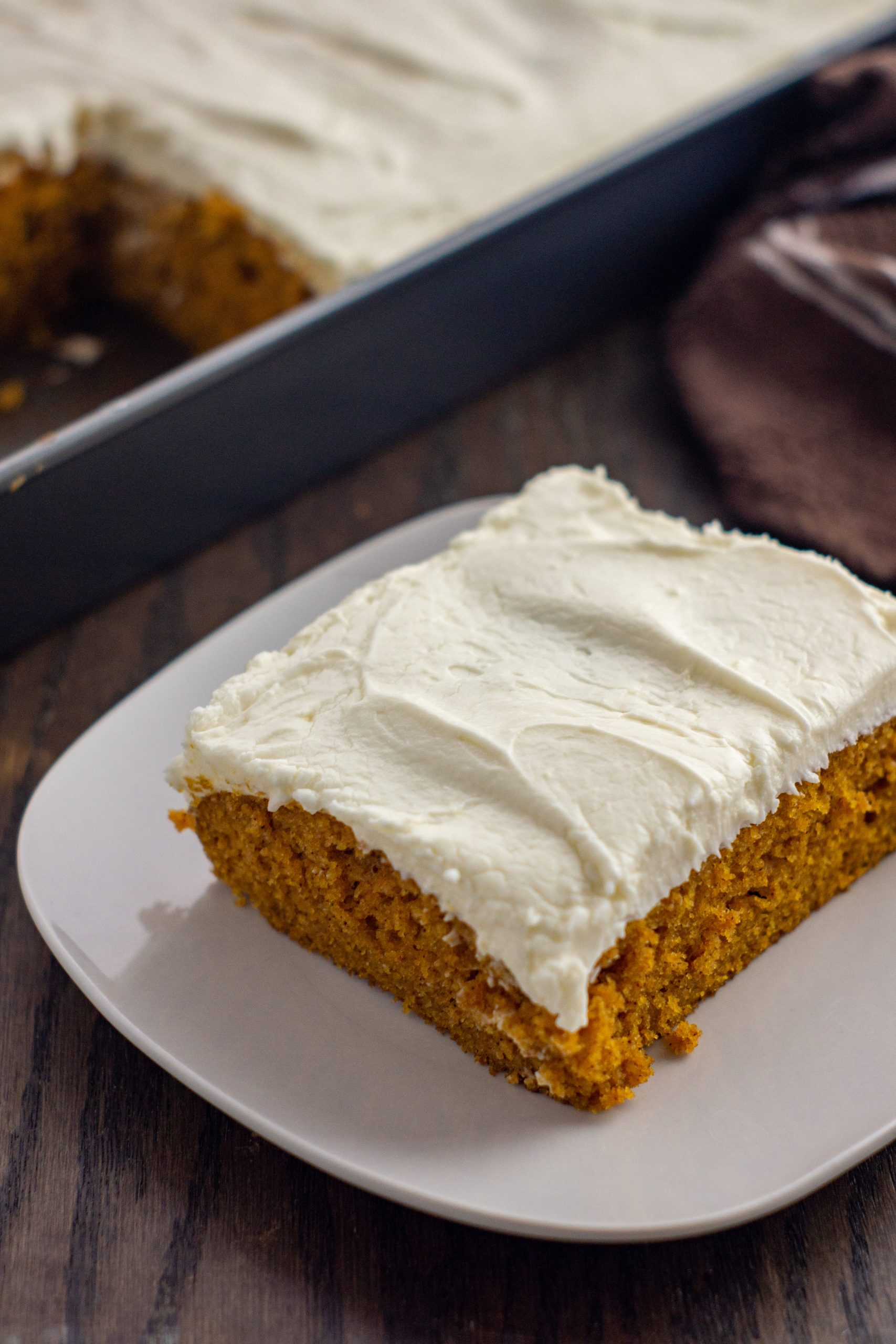 Calling all Pumpkin lovers! You're going to love this recipe for pumpkin cake with cream cheese frosting. This pumpkin spice cake with a homemade cream cheese frosting has the simplicity of a sheet cake with all the yummy flavors of pumpkin spice.