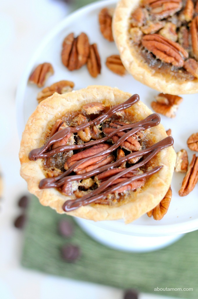 These mini chocolate pecan pies are a delicious treat for the holidays. Chocolate morsels are the perfect addition to the otherwise traditional miniature pecan pies.
