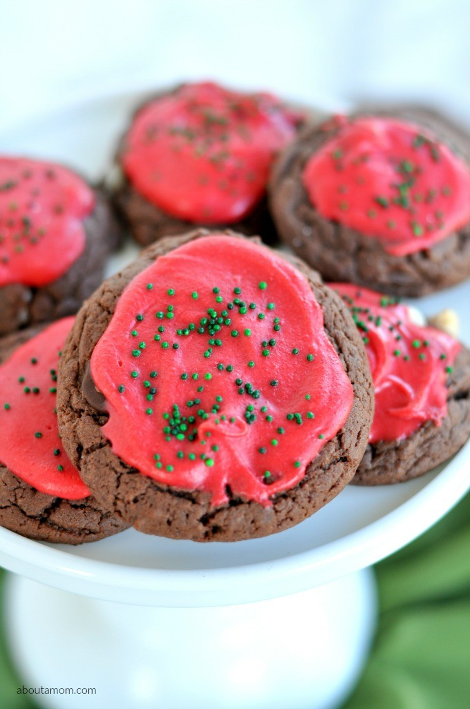 Decadent chocolate cake mix cookies with a mixture of white, dark, and semisweet chocolate chips. Frosted, sprinkled and festive for the holidays.