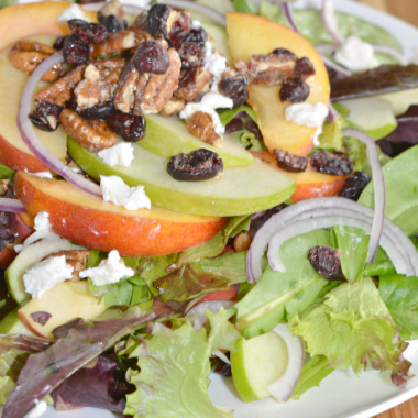 A delicious fruit and nut salad with citrus vinaigrette. Mixed greens, topped with peaches, crisp apple slices, red onion, pecans and goat cheese.