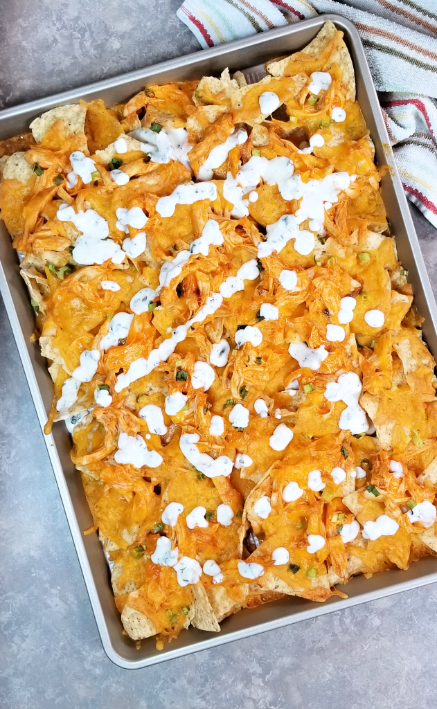 These sheet pan buffalo chicken nachos are cheesy and delicious, and made even better with a generous drizzle of ranch dressing. I live for the weekends and family night and this recipe for buffalo ranch chicken nachos is ideal for a laid-back family movie night or game night. Make these nachos for game day too!