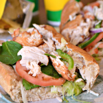 A delicious rotisserie-style chicken sandwich, made with tender, hand-pulled all white meat chicken, raised without antibiotics, and topped with flavorful crisp veggies on freshly baked bread.