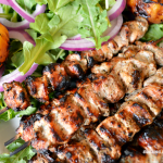 Delicious marinated grilled pork skewers served with grilled peaches, arugula and a refreshing cucumber mint sauce.