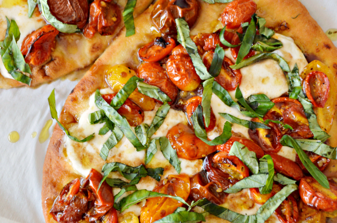 A roasted tomato and basil flatbread topped with extra virgin olive oil and balsamic reduction. This Caprese Flatbread Pizza recipe combines all the ingredients of a classic Caprese salad.