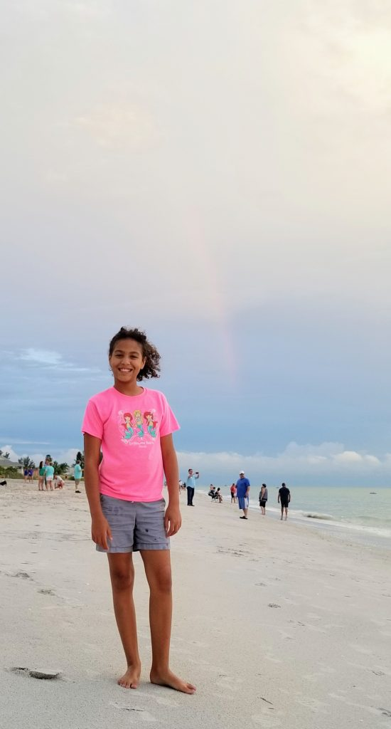 Florida Prepaid College Plans help parents give their children bright futures. Image of girl on the beach in Englewood, Florida with a rainbow in the background.
