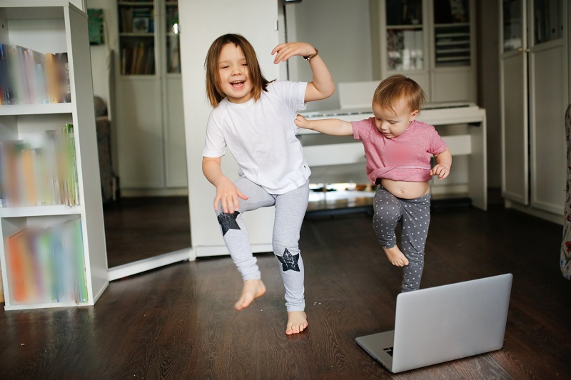5 Fun Ways to Get Kids Moving. Funny children dance, do sports exercises online. Authentic lifestyle in a real interior.