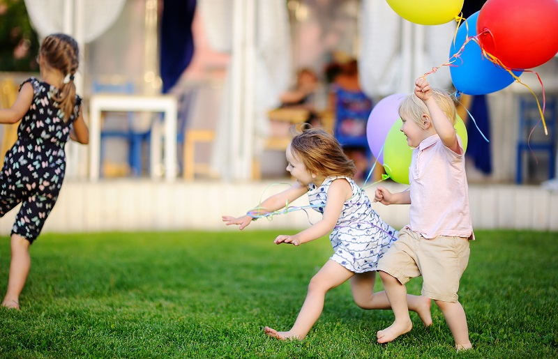 Little boy and girl having fun during celebrating birthday party. Happy child with with colorful balloons. Preschoolers or toddlers birthday party in outdoor cafe.