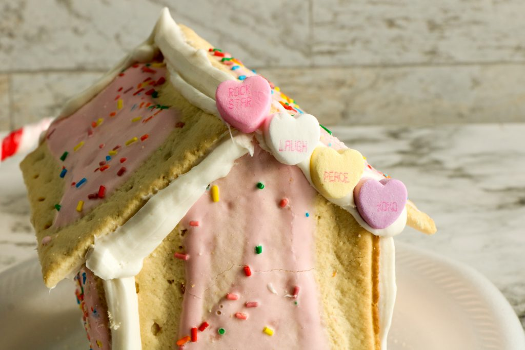 Decorating the Pop Tart House roofline with candy