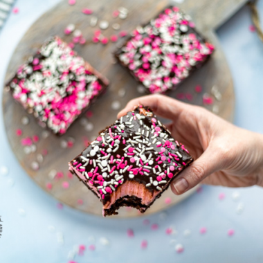 "Fudgy brownies with a pretty pink frosting and a chocolate ganache are topped with pretty Valentine's Day sprinkles. This decadent Valentine's Day treat is a great way to say ""I love you."" Sweetheart Brownies is such a sweet and easy Valentine's Day dessert."