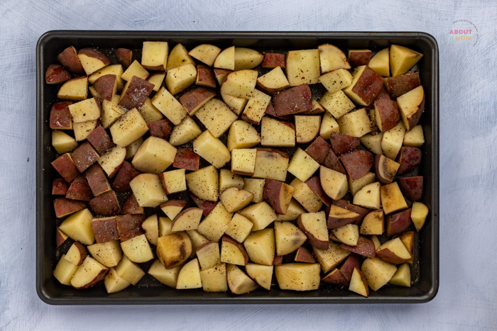 layer cubed potatos in rimmed baking sheet