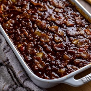 This is simply the best smokey baked beans recipe! This side dish comes together easily with canned beans, peppers, onions, molasses, brown sugar, a few dashes of liquid smoke and some additional pantry staples.